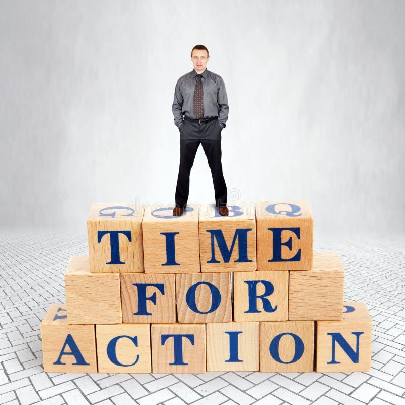 Den självsäkra mannen står på överkanten av högen av träkvarter med en appell Tid för handling fotografering för bildbyråer
