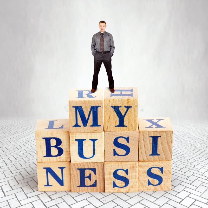 Den självsäkra mannen står på överkanten av högen av träkvarter med en text min affär royaltyfri foto