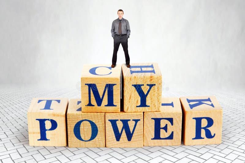 Den självsäkra mannen står på överkanten av högen av träkvarter med en text min makt arkivbilder