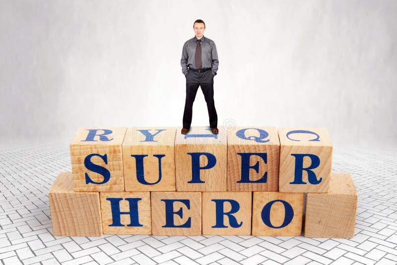 Den självsäkra mannen står på överkanten av högen av träkvarter med en toppen hjälte för text royaltyfri bild