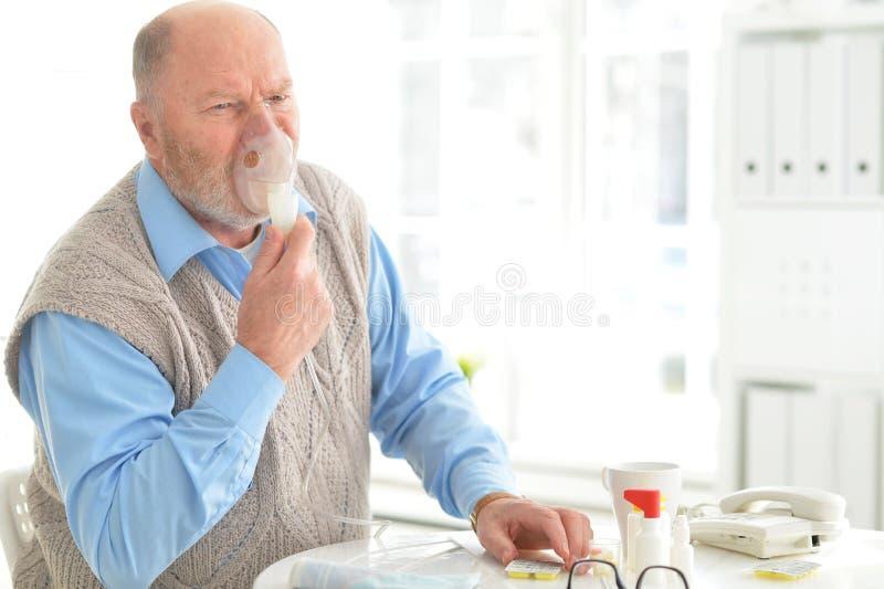 Den sjuka äldre mannen gör inandning royaltyfri foto