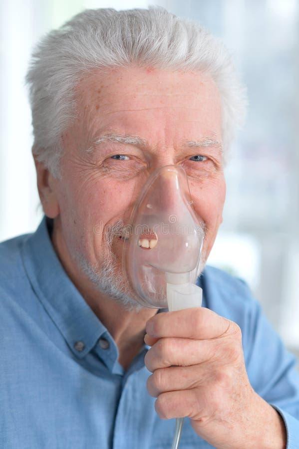 Den sjuka äldre mannen gör inandning royaltyfri fotografi