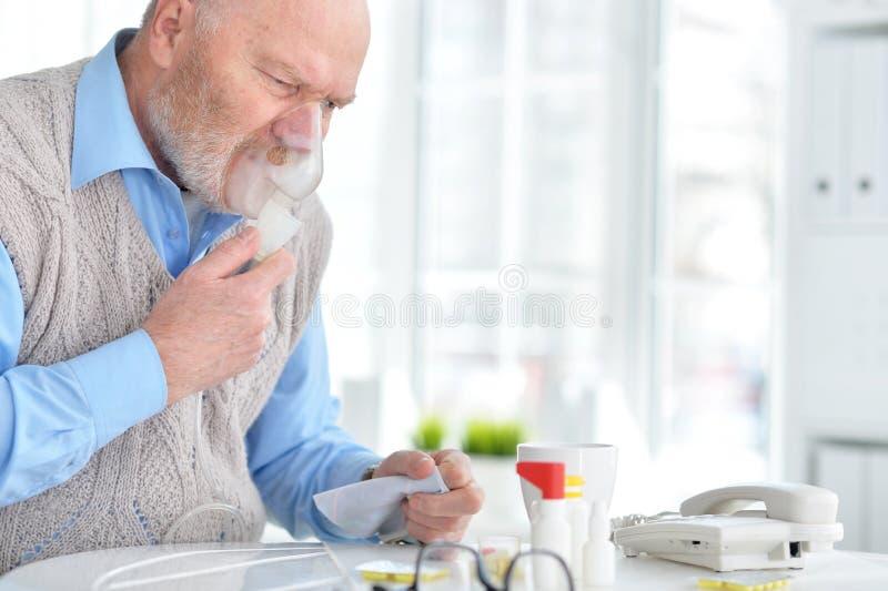 Den sjuka äldre mannen gör inandning arkivfoto