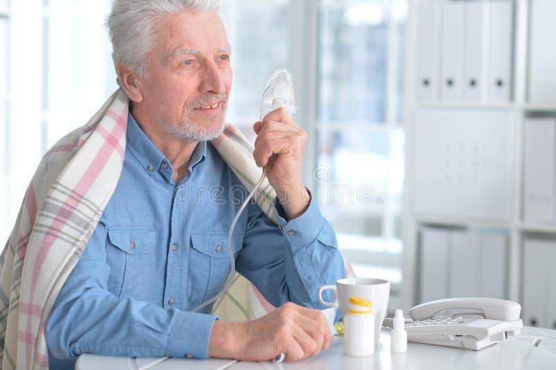 Den sjuka äldre mannen gör inandning royaltyfria foton