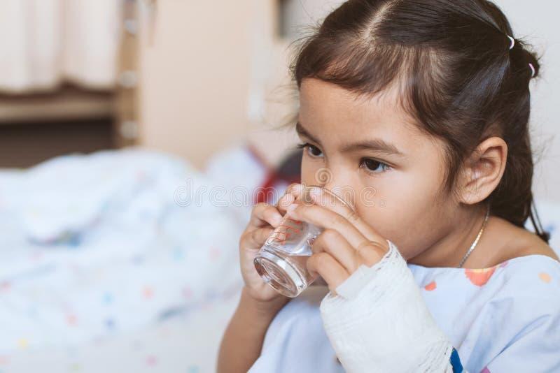 Den sjuka asiatiska flickahanden för det lilla barnet dricker sötvatten fotografering för bildbyråer