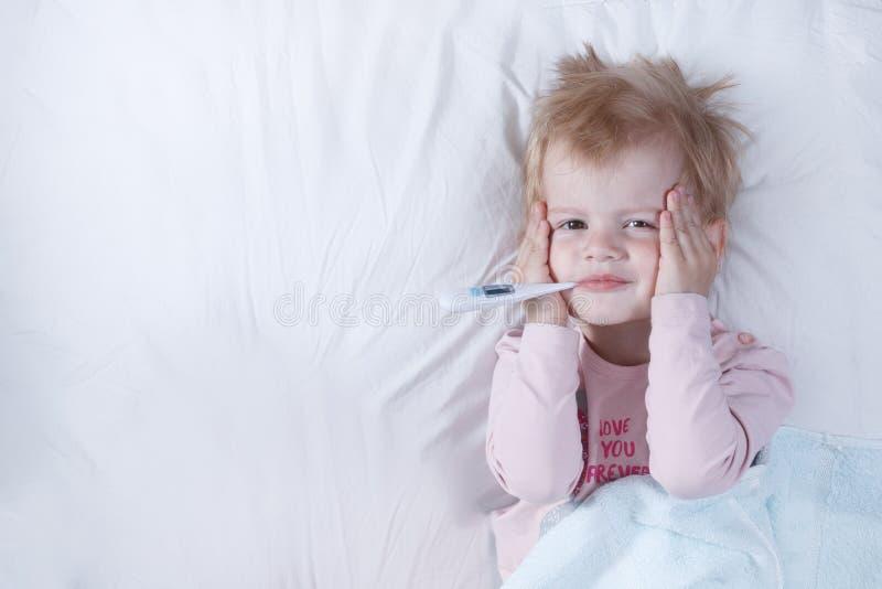 Den sjuka flickan, barnet med termometern i en mun, på en säng, begreppet av en sjukdom arkivbild