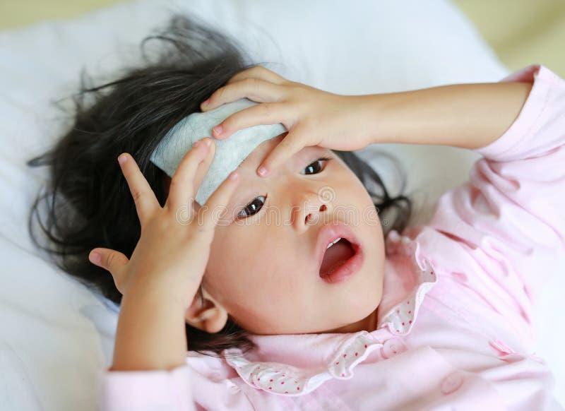 Den sjuka flickan som ligger på sängen med ett kallt, stelnar i framsidan royaltyfri bild