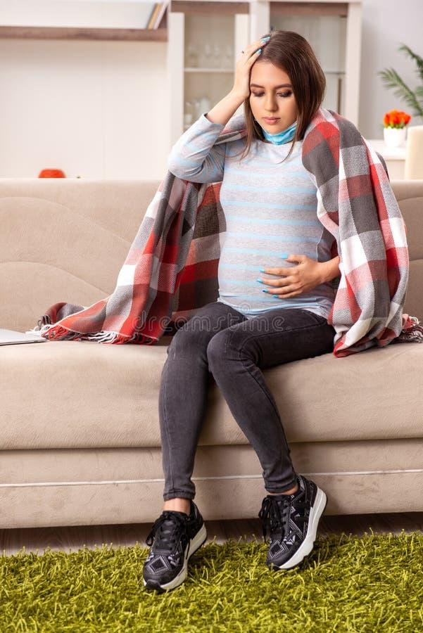 Den sjuka gravida kvinnan som hemma lider royaltyfri fotografi