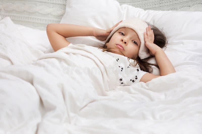 Den sjuka kalla flickan f?r det lilla barnet ligger i s?ng arkivbild