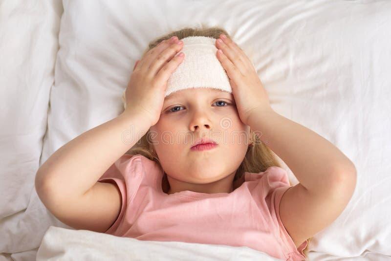 Den sjuka kalla flickan f?r det lilla barnet ligger i s?ng royaltyfria foton