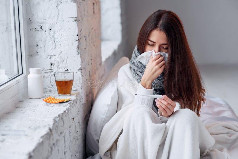Den sjuka kvinnan fångade kallt och att känna sig att sjukdomen och att nysa i papper torkar Closeup av den härliga sjukliga flic royaltyfria bilder