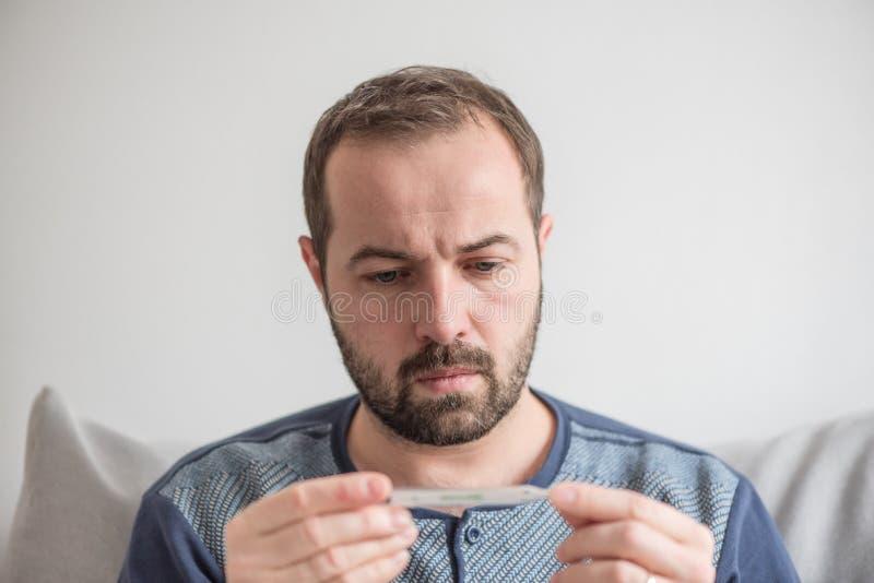 Den sjuka mannen kontrollerar kroppstemperaturen med en kvicksilvertermometer Tema av virus- sjukdomar, influensa, förkylningar M arkivbilder