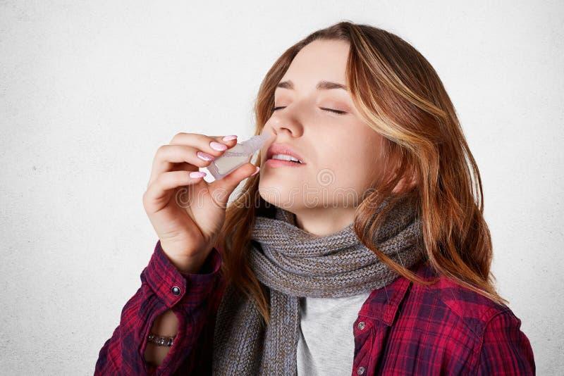 Den sjuka nätta kvinnan har blockerat näsan, nasala droppar för dripps, lider från rinnande näsa, över vitbetongbakgrund Allerg arkivfoton