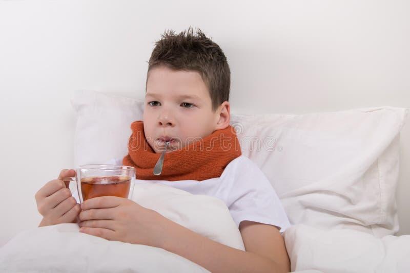 Den sjuka pojken dricker varmt te, utan att få ut ur säng royaltyfri bild