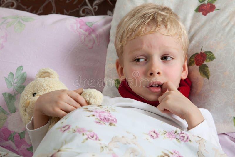 Den sjuka pojken ligger i underlag arkivfoto