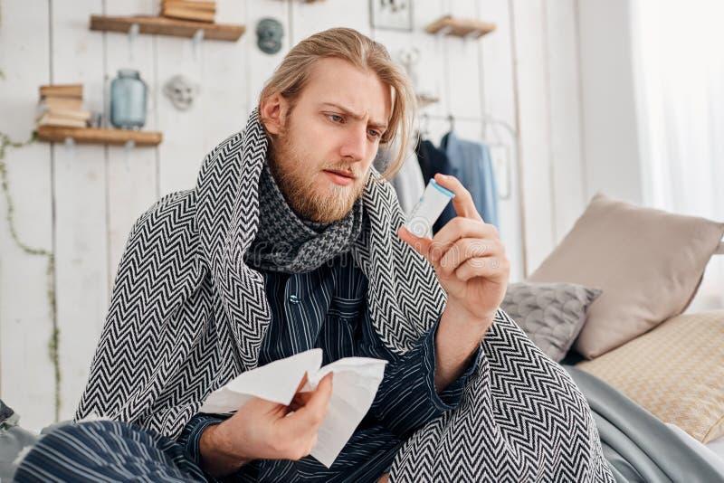 Den sjuka skäggiga blonda mannen i sleepwear sitter på säng som omges av filten, och kuddar, rynkar pannan, medan läsa royaltyfri bild