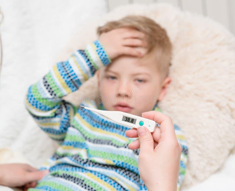 Den sjuka ungen med hög feber som lägger i säng och moder, kontrollerar temperaturen royaltyfri foto