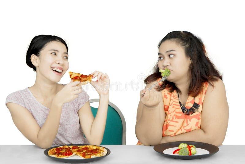 Den sjukligt feta kvinnablicken på vännen äter pizza royaltyfri fotografi