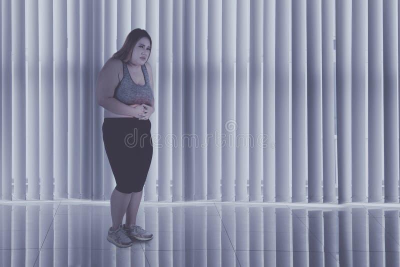 Den sjukligt feta kvinnan lider från buk- smärtar hemma royaltyfri fotografi