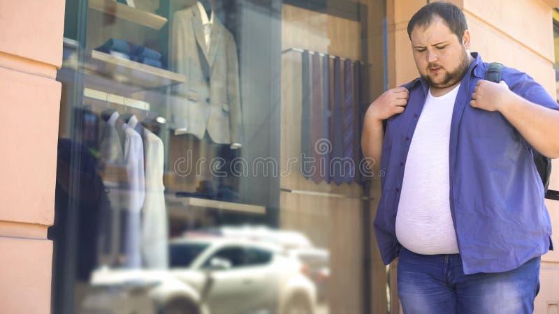 Den sjukligt feta mannen som ser SAD dräkter shoppar in, fönstret, det överviktiga problemet, motivation royaltyfri fotografi