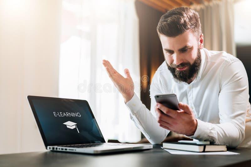 Den skäggiga affärsmannen i en vit skjorta sitter på en tabell framme av en bärbar dator med en incription som e-lär på skärmen arkivbilder