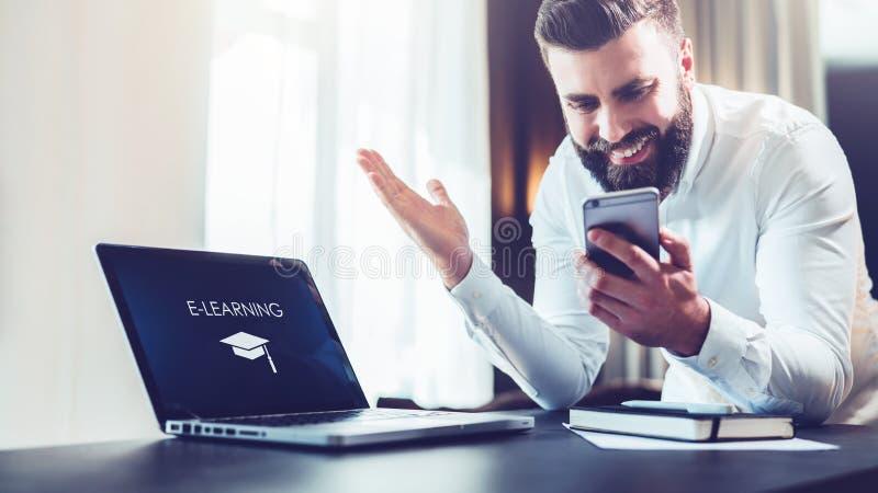 Den skäggiga affärsmannen i en vit skjorta sitter på en tabell framme av en bärbar dator med en inskrift som e-lär på skärmen fotografering för bildbyråer