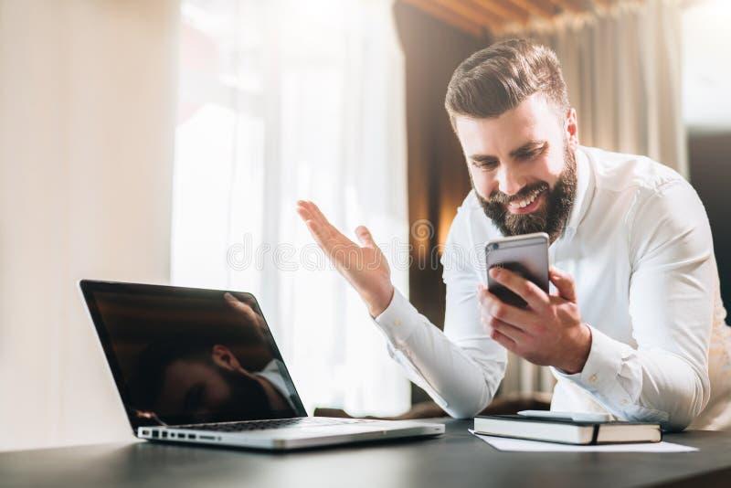 Den skäggiga affärsmannen i den vita skjortan sitter på tabellen framme av bärbara datorn och ser lyckligt skärmen av smartphonen royaltyfria foton