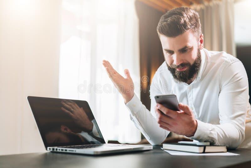 Den skäggiga affärsmannen i den vita skjortan sitter på tabellen framme av bärbara datorn och ser lyckligt skärmen av smartphonen arkivbild