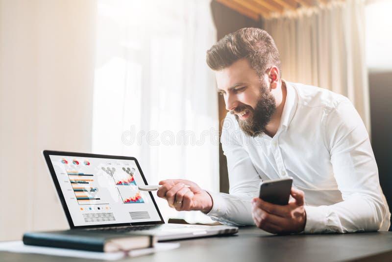Den skäggiga affärsmannen i den vita skjortan sitter på tabellen framme av datoren och att visa pennan på bärbar datorskärmen med royaltyfri foto