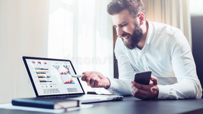 Den skäggiga affärsmannen i den vita skjortan sitter på tabellen framme av datoren och att visa pennan på bärbar datorskärmen med royaltyfria foton