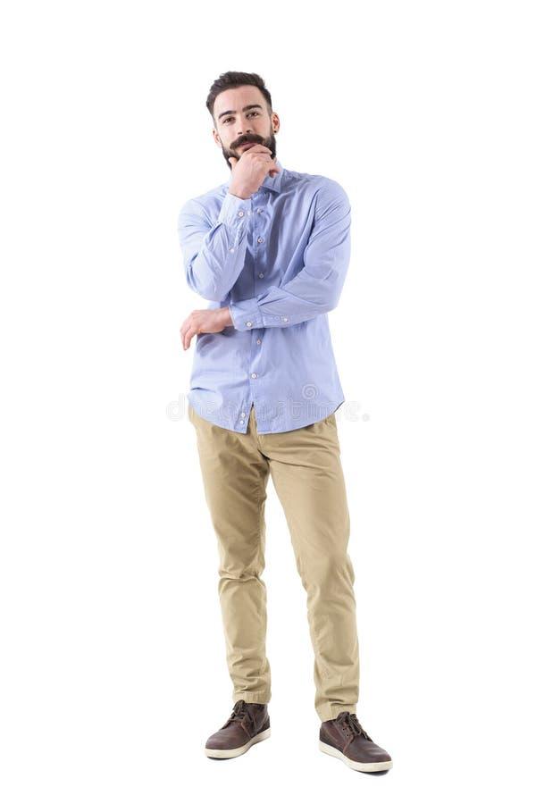 Den skäggiga affärsmannen som tänker med det rörande skägget för handen, ser kameran arkivfoto