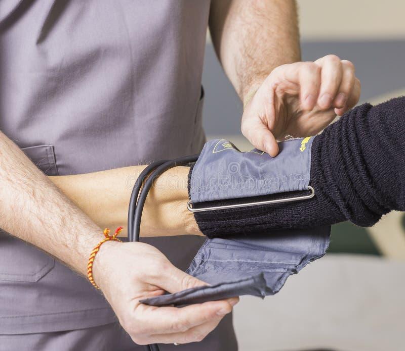 Den skäggiga doktorn som bär exponeringsglas, kontrollerar patientens blodtryck och puls fotografering för bildbyråer