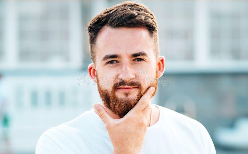Den skäggiga grabben gnider hans skägg på gatan royaltyfri foto