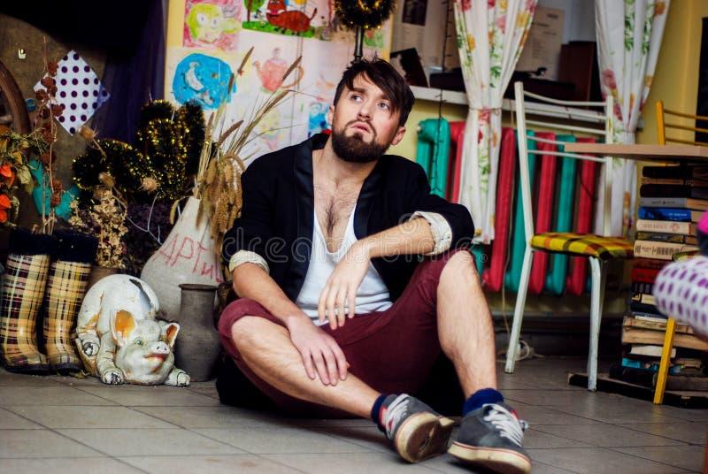 Den skäggiga grabben sitter på golvet royaltyfria foton