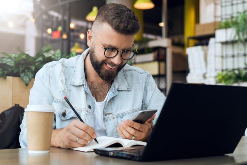 Den skäggiga hipstermannen sitter på tabellen framme av bärbara datorn och skriver i anteckningsboken, student förbereder sig för royaltyfri foto