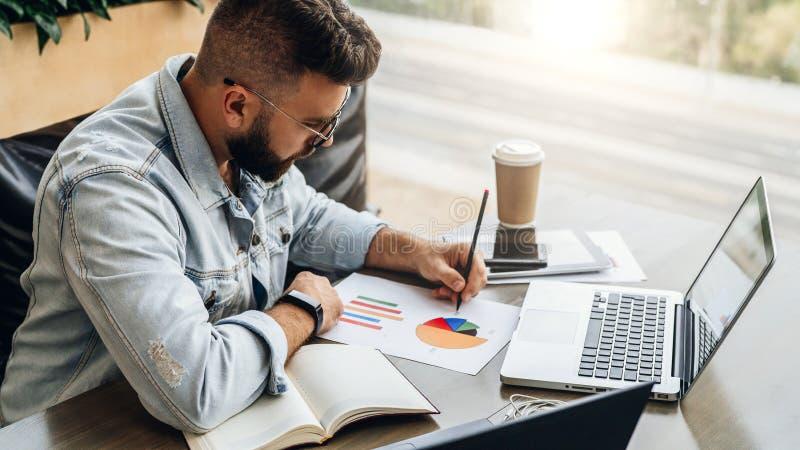 Den skäggiga hipstermannen sitter på tabellen och att arbeta på bärbara datorn och gör anmärkningar i diagrammet, grafen, diagram arkivfoto