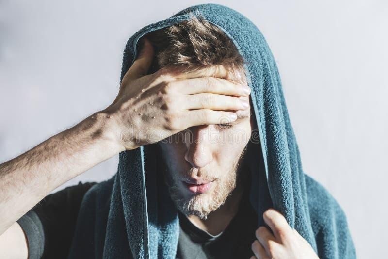 Den skäggiga idrottsmannen torkar av svettades droppar från hans framsida med handduken efter hård utbildning f royaltyfri bild