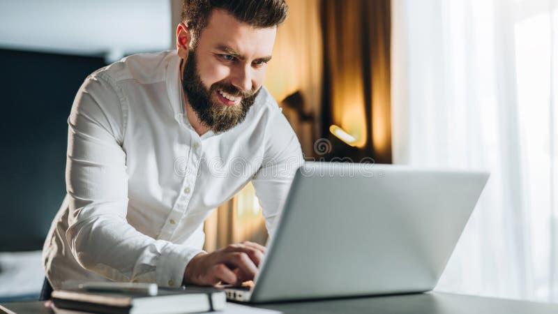 Den skäggiga le affärsmannen i skjorta skriver på bärbara datorn Mannen chef arbetar i regeringsställning på datoren, analyserar  arkivfoto