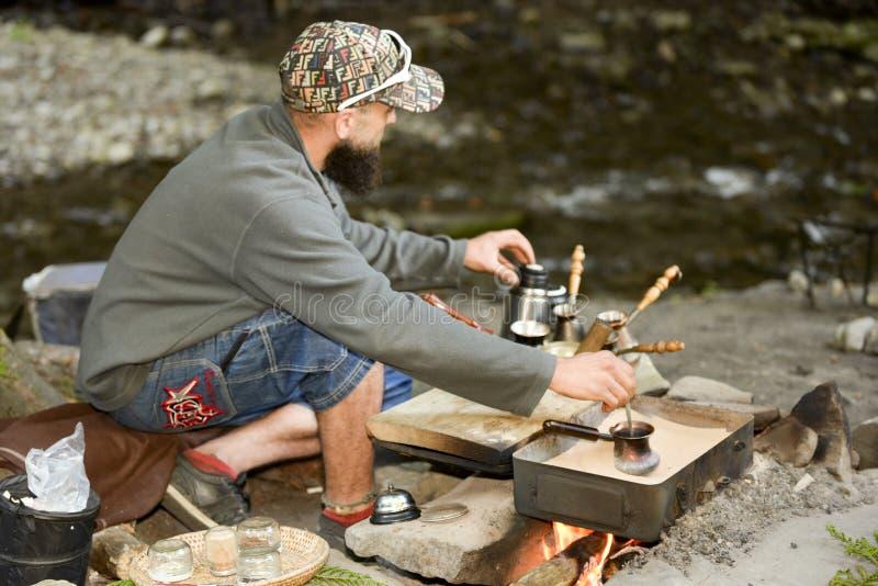 Den skäggiga mannen förbereder kaffe i bergen av Carpathiansna, Ukraina arkivbild
