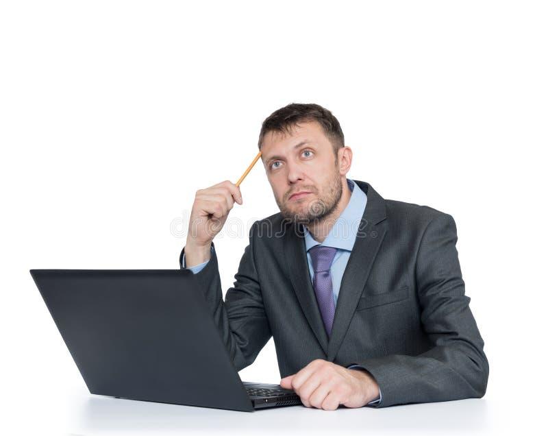 Den skäggiga mannen i dräkt tänker att sitta framme av bärbara datorn, isolerat på vit bakgrund royaltyfria bilder