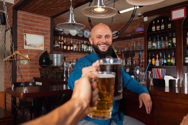 Den skäggiga mannen i stångfinkaexponeringsglas som rostar som dricker ölhållen, rånar, gladlynt vänmöte royaltyfria foton