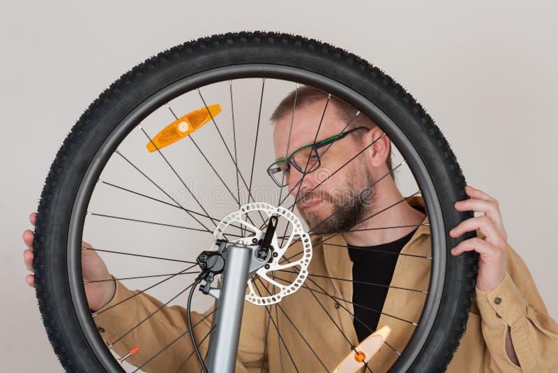 Den skäggiga mannen kontrollerar fästandet av framhjulet royaltyfri foto
