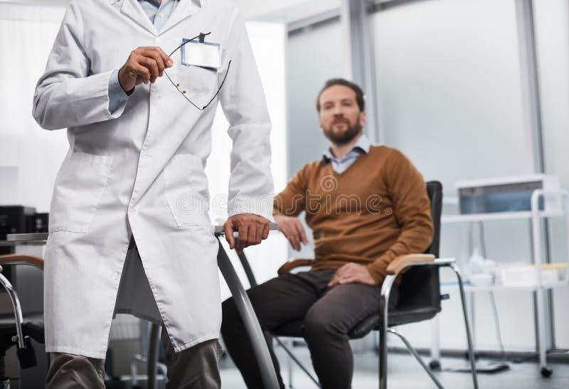 Den skäggiga mannen sitter på doktorskontoret fotografering för bildbyråer