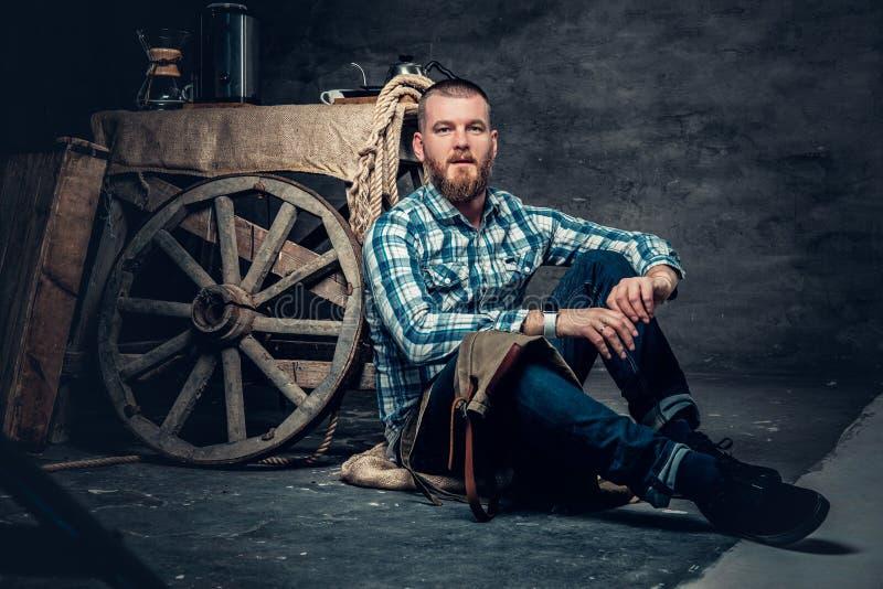 Den skäggiga mannen sitter på ett golv nära tabellen med en gammal träw royaltyfri bild