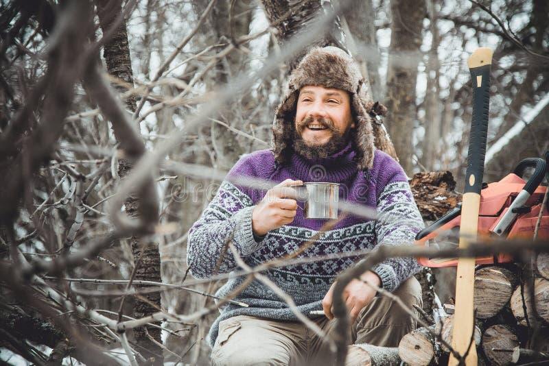 Den skäggiga mannen som dricker te i skogen, uppsökte skogshuggaren på vilar i vinter arkivfoto