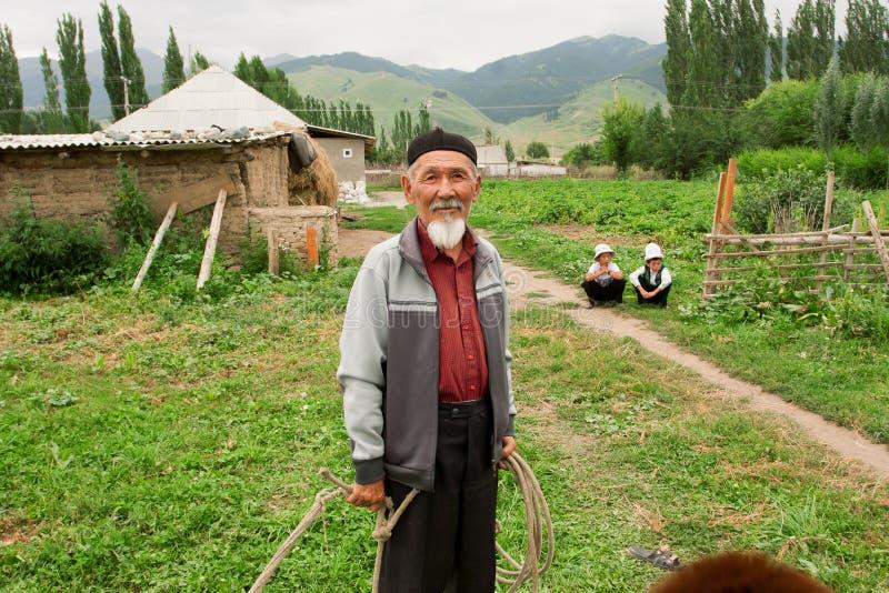 Den skäggiga pensionären har gyckel med barnbarn i en byKirgizistan royaltyfria bilder