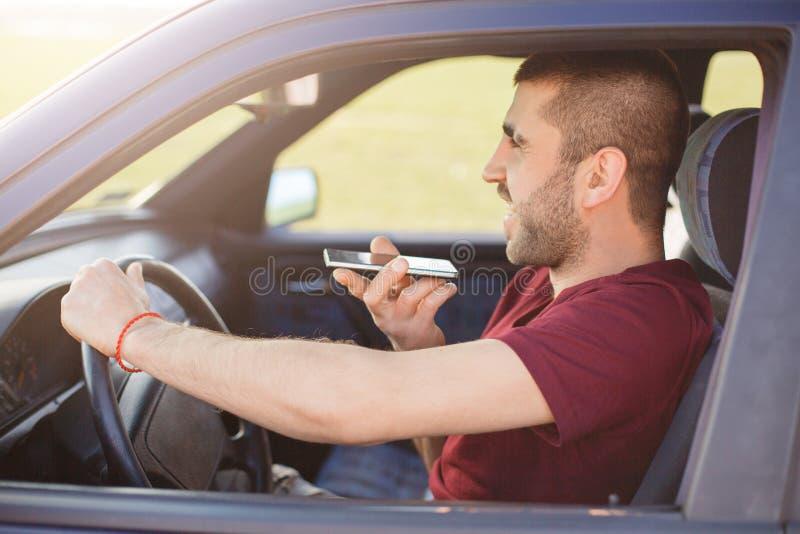 Den skäggiga tillfredsställda manliga chauffören kör bilen, talar via den smarta telefonen som tillfälligt som kläs är lycklig at arkivfoto