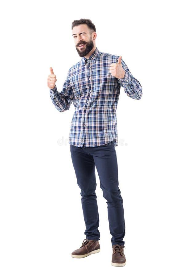 Den skäggiga unga vuxna affärsmannen i kontrollerad skjorta med tummar ler och blinkar upp på kameran royaltyfri fotografi
