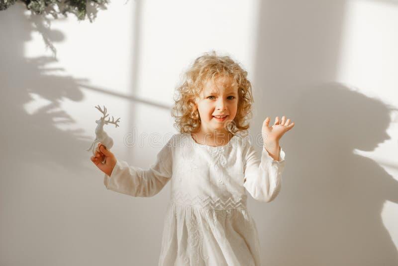 Den skämtsamma gladlynta lilla härliga flickan med blont lockigt hår spelar med leksakhjortar, den iklädda festliga vita klänning arkivfoto