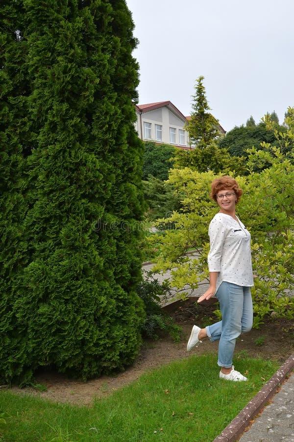 Den skämtsamma kvinnan av genomsnittliga årskostnader bland träd i parkera royaltyfria foton